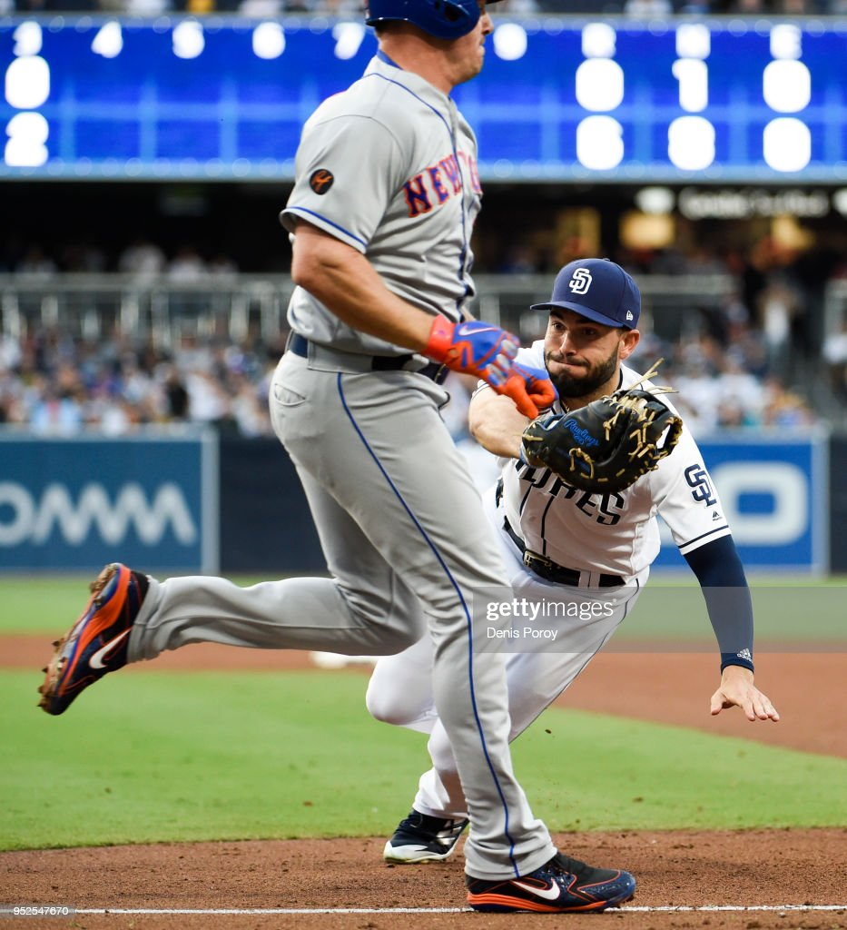 Eric Hosmer #30 of the San Diego Padres tags out Jay Bruce #19 of the New York Mets as he heads for first base during the fourth inning of a baseball game at PETCO Park on April 28, 2018 in San Diego, California.