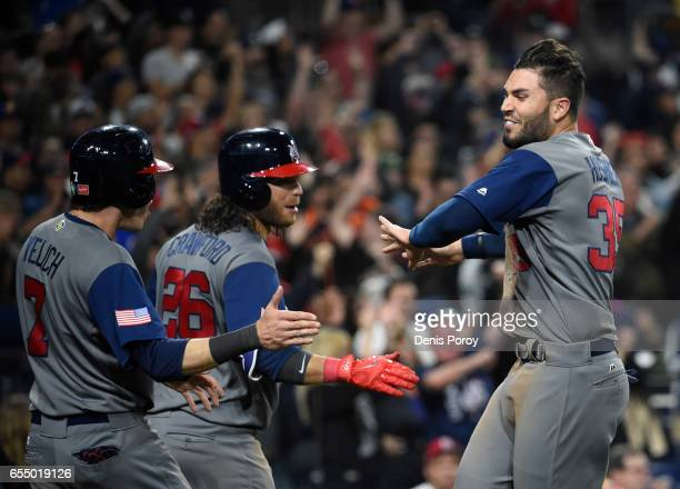 Eric Hosmer of the United States right is congratulated by Brandon Crawford and Christian Yelich after scoring during the eighth inning of the World...