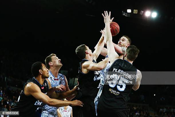 Eric Jacobsen of Adelaide goes up against Kirk Penney and Alex Pledger of New Zealand during the round four NBL match between the New Zealand...