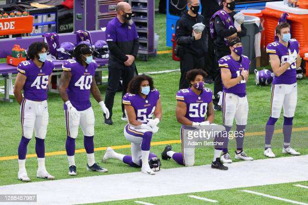 Eric Kendricks and Eric Wilson of the Minnesota Vikings kneel on the sideline during the national anthem before the game against the Carolina...