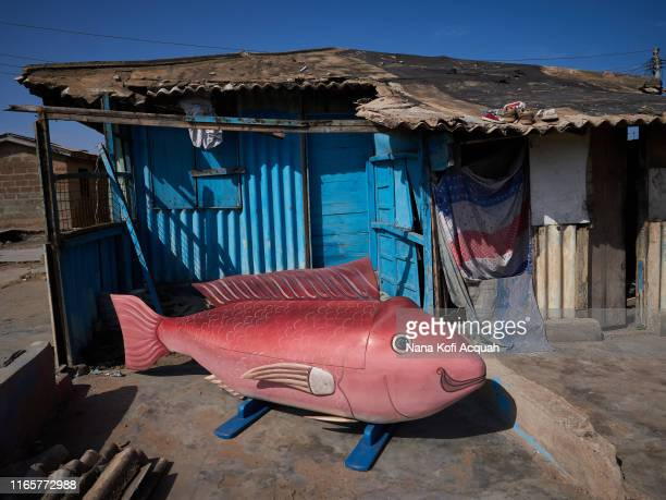 Eric Kpakpo Addotey's pink fish fantasy coffin sits near an abandoned wooden shack on June 21, 2019 in La Accra, Ghana. A fish fantasy coffin is...