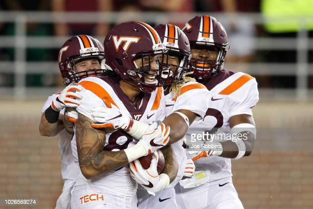 Eric Kumah of the Virginia Tech Hokies celebrates with teammates after returning a blocked punt for a touchdown in the second quarter of the game...