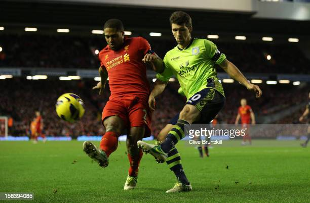 Eric Lichaj of Aston Villa clears from Glen Johnson of Liverpool during the Barclays Premier League match between Liverpool and Aston Villa at...