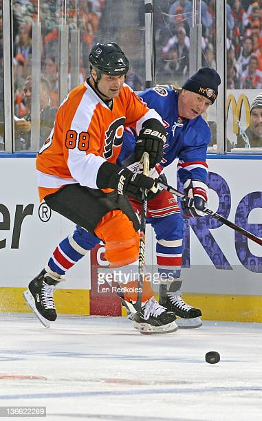 Eric Lindros of the Philadelphia Flyers battles for the puck against the New York Rangers during the Alumni Game prior to the 2012 NHL Bridgestone...