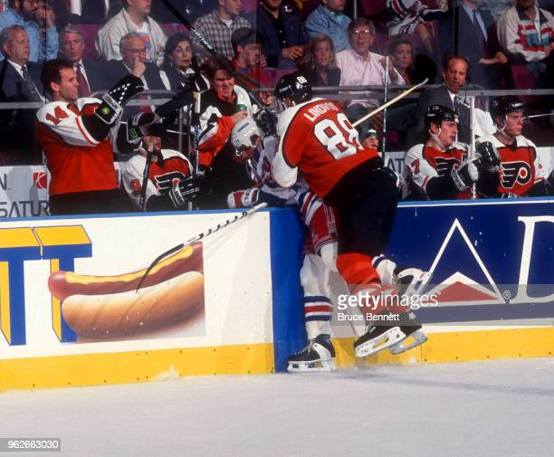 Eric Lindros of the Philadelphia Flyers checks Mark Osborne of the New York Rangers into the Flyers bench during Game 4 of the Conference SemiFinals...