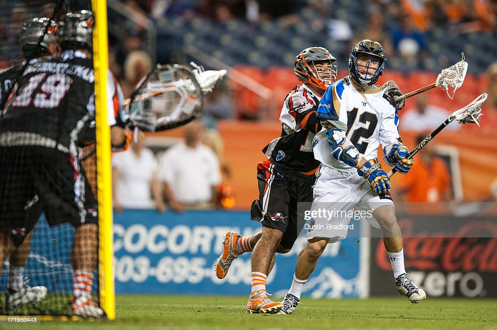Eric Lusby #12 of the Charlotte Hounds looks for a shot as he is covered by Justin Pennington #14 of the Denver Outlaws during a Major League Lacrosse game at Sports Authority Field at Mile High on June 29, 2013 in Denver, Colorado. The Outlaws beat the Hounds 17-11 and improved to 9-0 on the season.