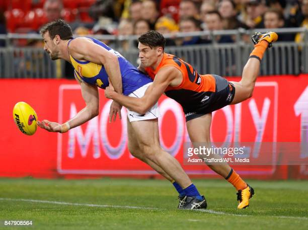 Eric Mackenzie of the Eagles is tackled by Josh Kelly of the Giants during the 2017 AFL First Semi Final match between the GWS Giants and the West...