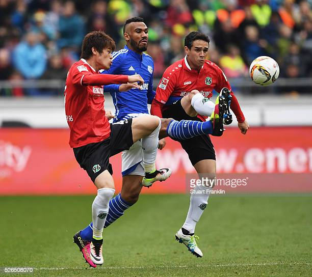 Eric Maxim Choupo-Moting of Schalke is challenged by Hiroki Sakai and Manuel Schmiedebach of Hannover during the Bundesliga match between Hannover 96...