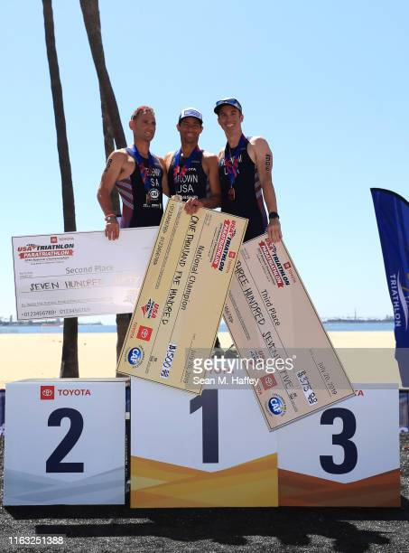 Eric McElvenny second place, Jamie Brown first place, and Joel Rosinbum third place react on the podium for the Male PTS4 division of the Legacy...