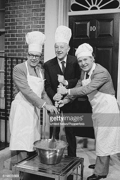 Eric Morecambe and Ernie Wise of English comedy duo Morecambe and Wise pictured together with actor Alec Guinness in centre stirring a pot outside a...