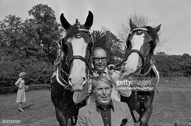 Eric Morecambe behind and Ernie Wise at front from comedy double act Morecambe and Wise posed together between two Courage brewery Shire horses in...