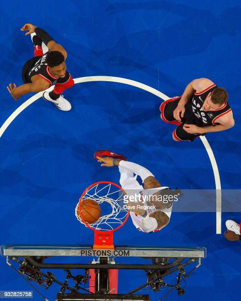 Eric Moreland of the Detroit Pistons dunks the ball in front of Malcolm Miller and Jakob Poeltl of the Toronto Raptors in the second half of an NBA...