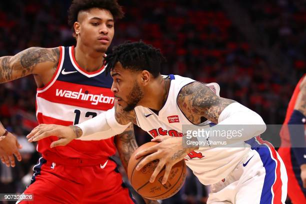 Eric Moreland of the Detroit Pistons tries to drive around Kelly Oubre Jr #12 of the Washington Wizards during the first half at Little Caesars Arena...