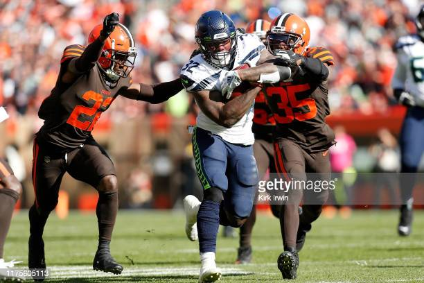 Eric Murray of the Cleveland Browns and Jermaine Whitehead combine to tackle Chris Carson of the Seattle Seahawks during the third quarter at...