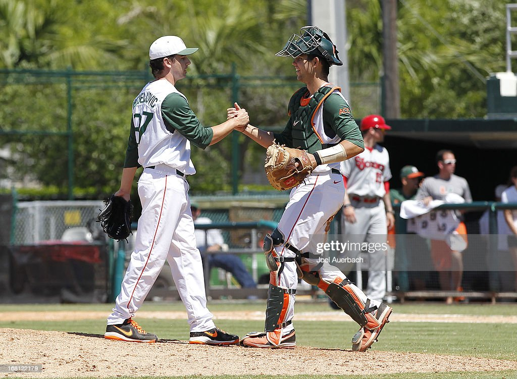 Eric Nedeljkovic #37 is congratulated by Garrett Kennedy #40 of the Miami Hurricanes after the final out of the game against the St John's Red Storm on May 5, 2013 at Alex Rodriguez Park at Mark Light Field in Coral Gables, Florida. Miami defeated St John's 6-4 and swept the weekend series.