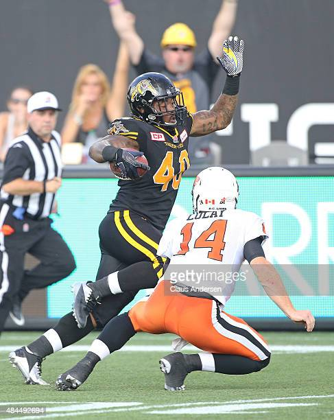 Eric Norwood of the Hamilton TigerCats steps around quarterback Travis Lulay of the BC Lions for a touchdown during a CFL football game at Tim...