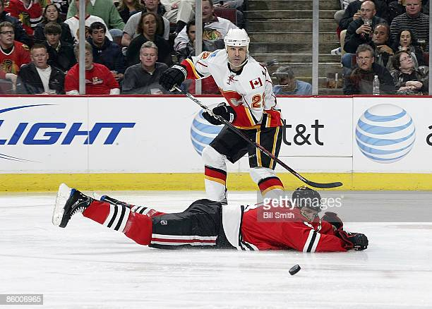 Eric Nystrom of the Calgary Flames watches the puck fly through the air as Matt Walker of the Chicago Blackhawks watches from flat on the ice during...