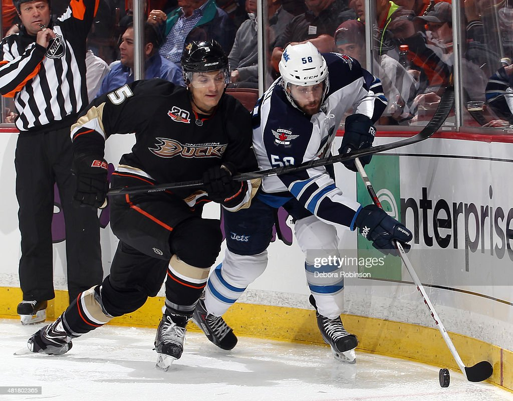 Eric O'Dell #58 of the Winnipeg Jets battles for the puck against Luca Sbisa #5 of the Anaheim Ducks on March 31, 2014 at Honda Center in Anaheim, California.