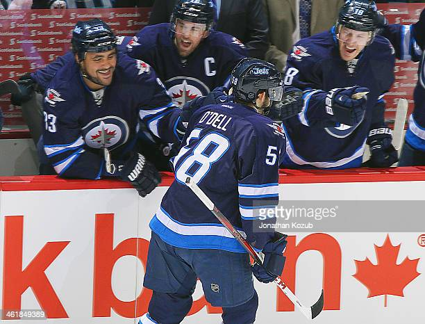 Eric O'Dell of the Winnipeg Jets is congratulated by teammates Dustin Byfuglien, Andrew Ladd and Bryan Little at the bench after scoring his first...