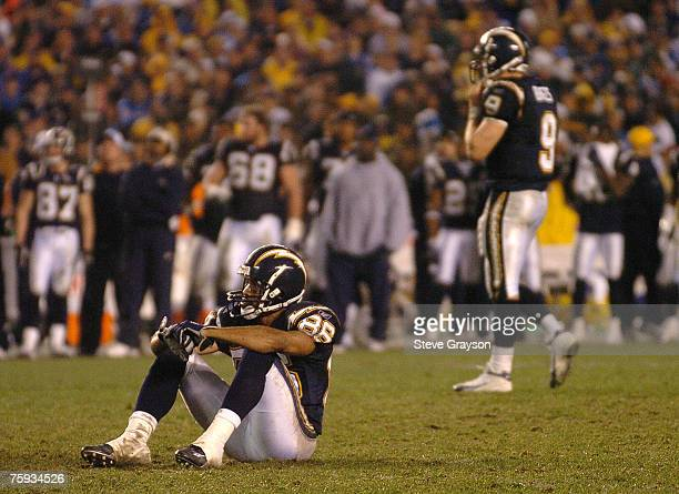 Eric Parker of the San Diego Chargers sits on the turf as Drew Brees looks on in the second half of during their contest against the New York Jets in...