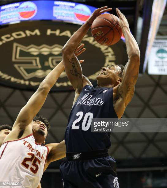 Eric Parrish of the Akron Zips hauls in a rebound ahead of Bennie Boatwright of the USC Trojans during the first half of their game at the Stan...