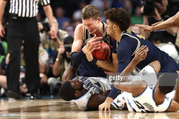 Eric Paschall of the Villanova Wildcats competes for the ball with Moritz Wagner and Isaiah Livers of the Michigan Wolverines in the first half...