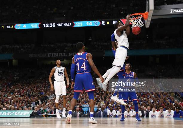 Eric Paschall of the Villanova Wildcats dunks in the first half against Malik Newman and Devonte' Graham of the Kansas Jayhawks during the 2018 NCAA...