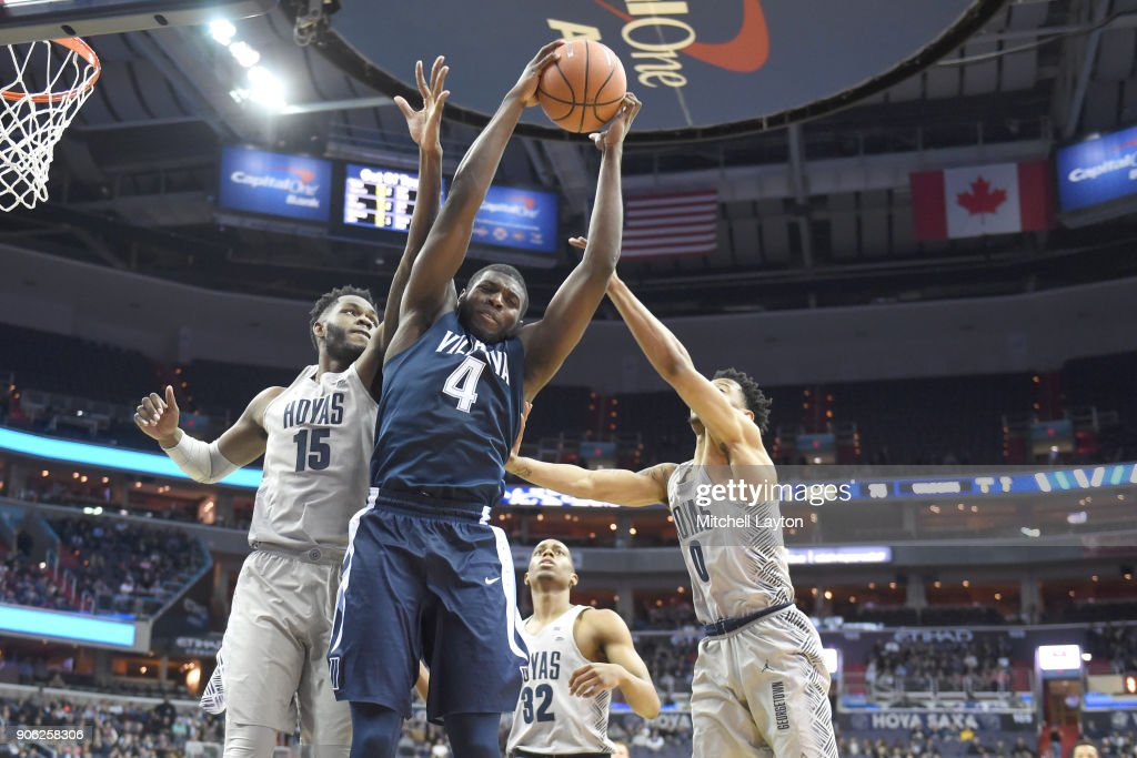 Eric Paschall #4 of the Villanova Wildcats pulls down a rebound over Jessie Govan #15 and Johavon Blair #0 of the Georgetown Hoyas during a college basketball game at the Capital One Arena on January 17, 2018 in Washington, DC.
