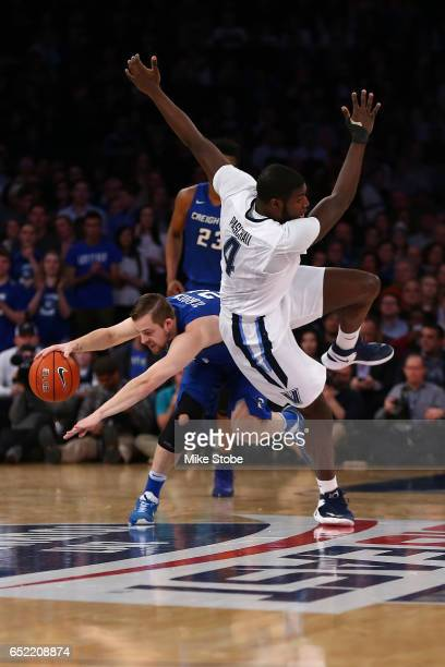 Eric Paschall of the Villanova Wildcats trips up over Isaiah Zierden of the Creighton Bluejays during the Big East Basketball Tournament -...