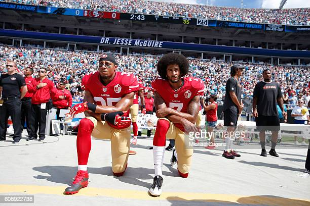 Eric Reid and Colin Kaepernick of the San Francisco 49ers kneel on the sideline during the anthem prior to the game against the Carolina Panthers at...