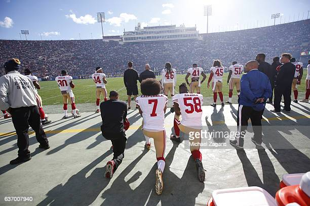 Eric Reid Colin Kaepernick and Eli Harold of the San Francisco 49ers kneel on the sideline during the anthem prior to the game against the Los...