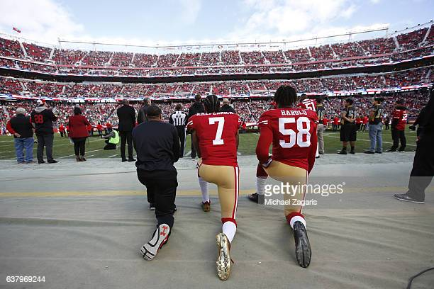 Eric Reid, Colin Kaepernick and Eli Harold of the San Francisco 49ers kneel on the sideline, during the anthem, prior to the game against the Seattle...