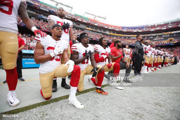 Eric Reid Marquise Goodwin and Adrian Colbert of the San Francisco 49ers kneel with teammates during the anthem prior to the game against the...
