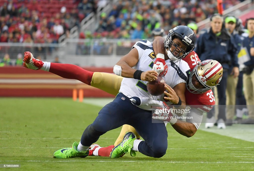 Eric Reid #35 of the San Francisco 49ers drags down Russell Wilson #3 of the Seattle Seahawks from behind during their NFL football game at Levi's Stadium on November 26, 2017 in Santa Clara, California.