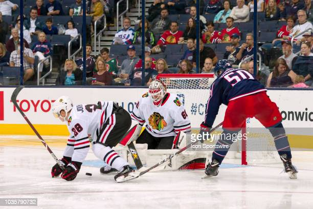 Eric Robinson of the Columbus Blue Jackets attempts a shot on goal as Henri Jokiharju of the Chicago Blackhawks and Collin Delia of the Chicago...