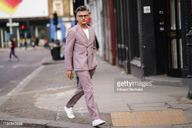 Eric Rutherford wears a pale purple blazer jacket pants white sneakers shoes glasses during London Fashion Week Men's June 2019 on June 09 2019 in...