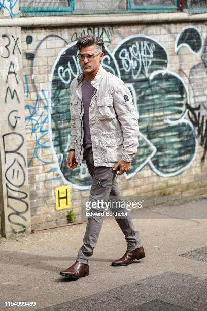 Eric Rutherford wears glasses a white jacket a purple top gray pants brown leather shoes during London Fashion Week Men's June 2019 on June 09 2019...