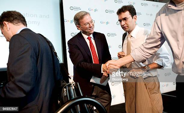 Eric Schmidt chief executive officer of Google shakes the hand of a reporter as University of Pittsburgh PhD student Miguel TorresUrquidy center...
