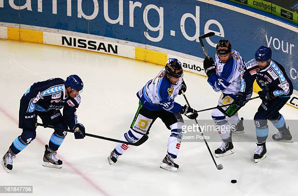 Eric Schneider and Robert Collins of Hamburg and Rene Roethke of Straubing compete for the puck during the DEL game between Hamburg Freezers and...