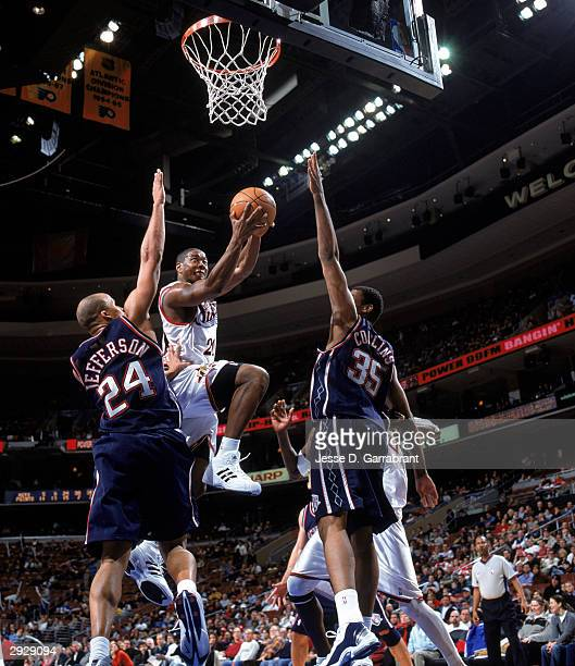 Eric Snow of the Philadelphia 76ers drives to the basket against Richard Jefferson and Jason Collins of the New Jersey Nets during the NBA game at...