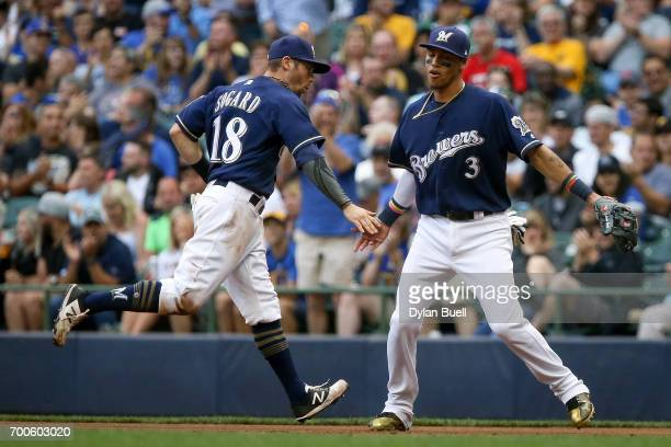 Eric Sogard and Orlando Arcia of the Milwaukee Brewers celebrate after turning a double play in the second inning against the Pittsburgh Pirates at...