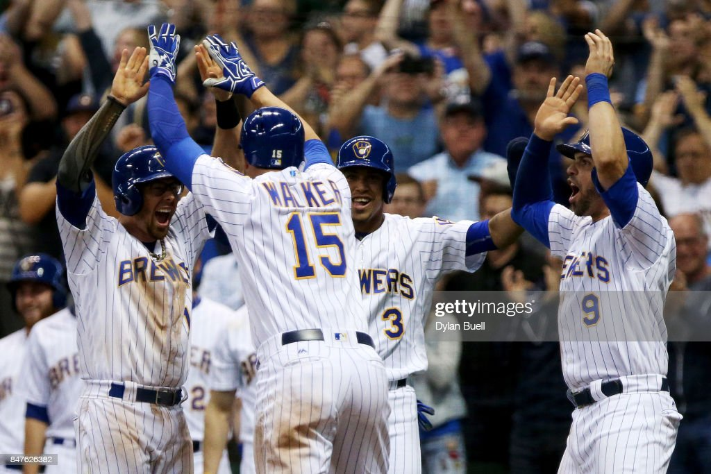 Eric Sogard #18, Neil Walker #15, Orlando Arcia #3, and Manny Pina #9 of the Milwaukee Brewers celebrate after Walker hit a grand slam in the eighth inning against the Miami Marlins at Miller Park on September 15, 2017 in Milwaukee, Wisconsin.
