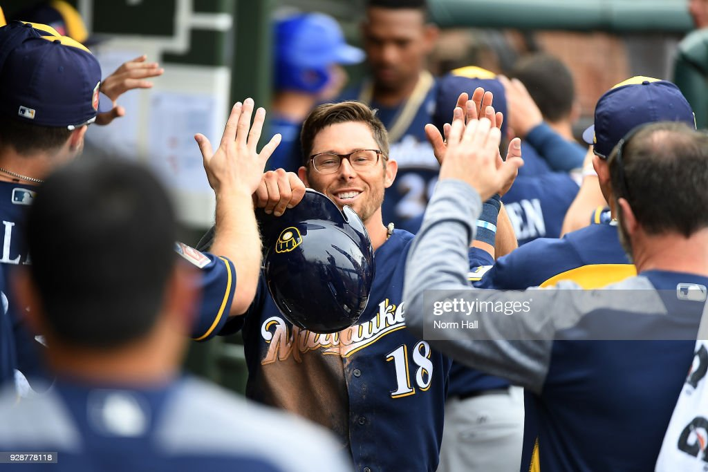 Eric Sogard #18 of the Milwaukee Brewers celebrates with teammates in the dugout after scoring on a double by Hernan Perez #14 during the fifth inning of a spring training game against the Kansas City Royals at Surprise Stadium on March 7, 2018 in Surprise, Arizona.