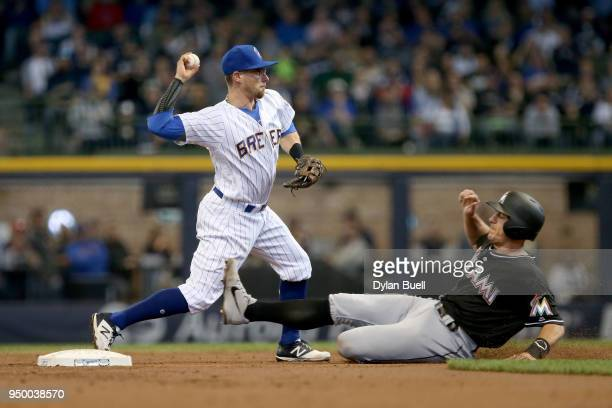 Eric Sogard of the Milwaukee Brewers turns a double play past JT Realmuto of the Miami Marlins in the third inning at Miller Park on April 22 2018 in...