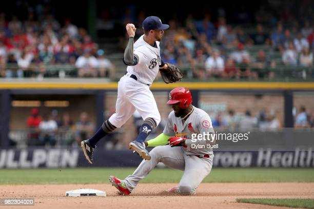 Eric Sogard of the Milwaukee Brewers turns a double play past Marcell Ozuna of the St Louis Cardinals in the eighth inning at Miller Park on June 23...