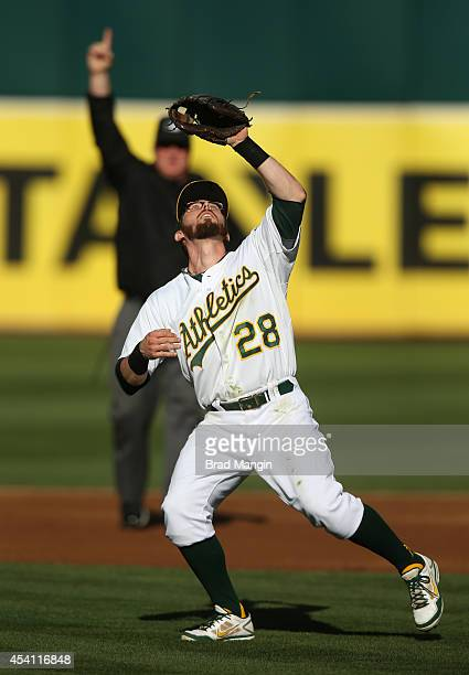 Eric Sogard of the Oakland Athletics catches a pop up at second base as umpire Bill Miller calls for the infield fly rule in the background during...