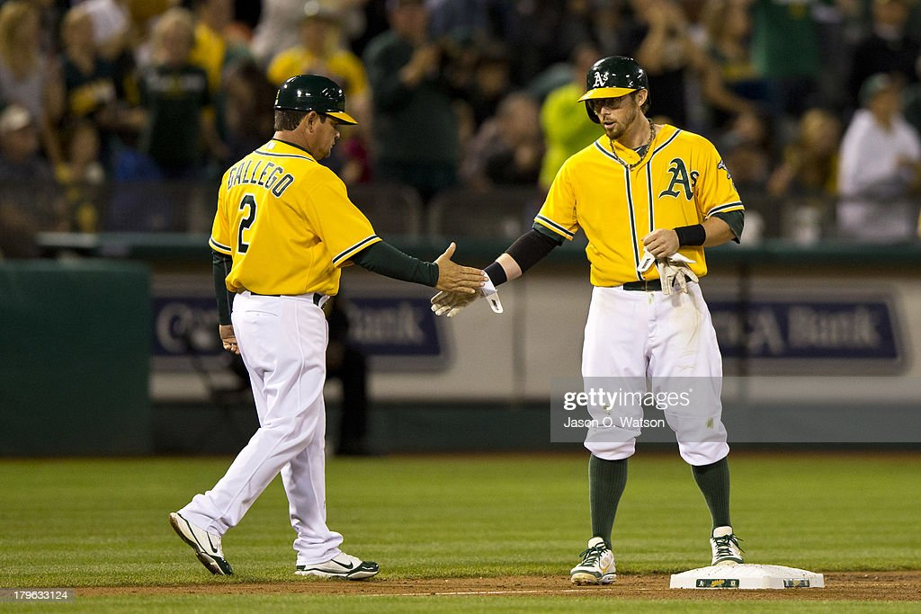 Eric Sogard #28 of the Oakland Athletics is congratulated by third base coach Mike Gallego #2 after hitting a triple against the Houston Astros during the eighth inning at O.co Coliseum on September 5, 2013 in Oakland, California.