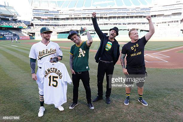 Eric Sogard of the Oakland Athletics presents Billie Joe Armstrong Mike Dirnt and Tre Cool of Green Day with special Athletics jerseys prior to the...