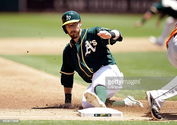 Eric Sogard of the Oakland Athletics slides safely in to third base for a stolen base in the third inning of their game against the Houston Astros at...