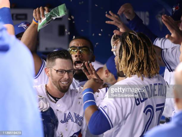 Eric Sogard of the Toronto Blue Jays is congratulated by Teoscar Hernandez and Vladimir Guerrero Jr #27 after hitting a solo home run in the first...